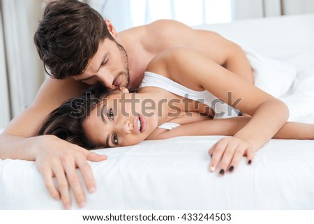 Young beautiful passionate couple in bed
