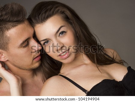 Young beautiful passionate couple on gray studio background