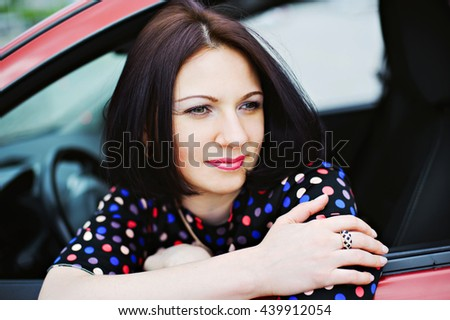 Young beautiful pensive woman smiling, looking out the car window to side. - stock photo