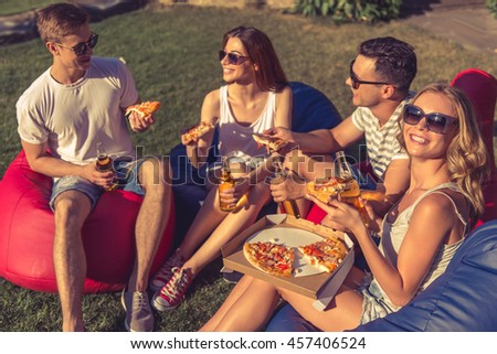 Young beautiful people in casual clothes and sun glasses are eating pizza, communicating and smiling, sitting on bean bag chairs while resting outdoors - stock photo