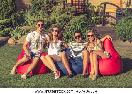 Young beautiful people in casual clothes and sun glasses are looking at camera and smiling, sitting on bean bag chairs while resting outdoors
