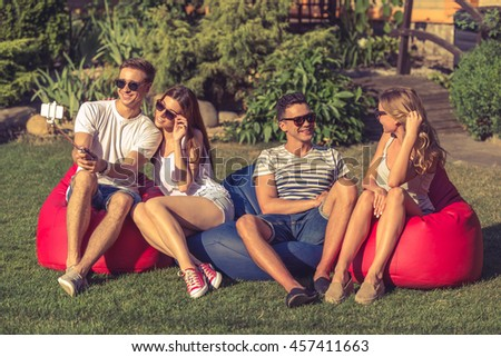 Young beautiful people in casual clothes and sun glasses are sitting on bean bag chairs while resting outdoors. One couple is making selfie, the other is talking