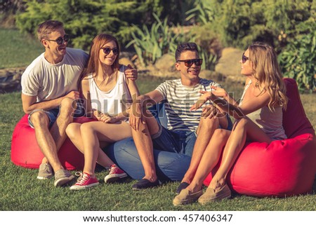 Young beautiful people in casual clothes and sun glasses are talking and smiling, sitting on bean bag chairs while resting outdoors