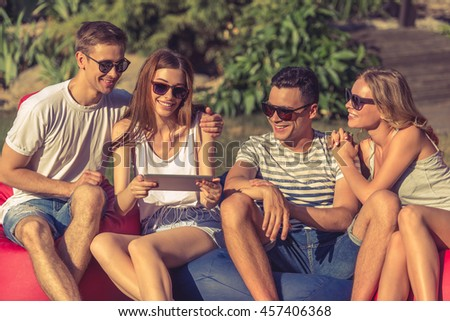 Young beautiful people in casual clothes and sun glasses are using a digital tablet and smiling, sitting on bean bag chairs while resting outdoors - stock photo