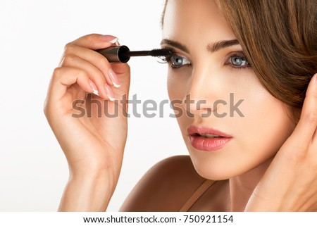 young beautiful perfect model applying professional mascara on white