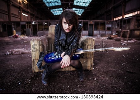 Young beautiful performer posing with her electric guitar.