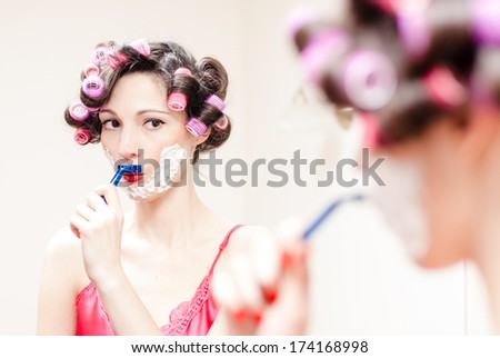 Young beautiful pinup woman shaving mustache with razor and foam - stock photo
