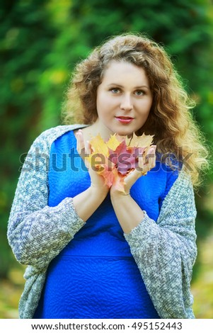 young beautiful plussize model in the autumn park