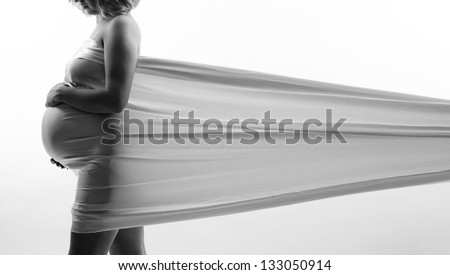 Young beautiful pregnant girl and in the sensory underwear on the bright background - stock photo