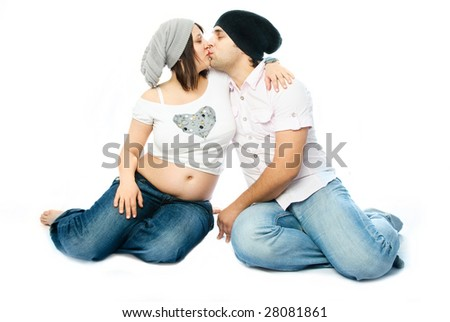 young beautiful pregnant woman and her husband embracing and kissing - stock photo