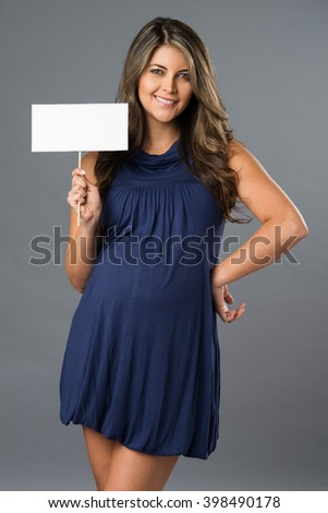 Young beautiful pregnant woman holding white blank paper - stock photo