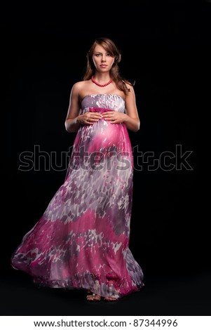 Young beautiful pregnant woman in pink dress - stock photo