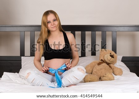 young beautiful pregnant woman sitting on a bed