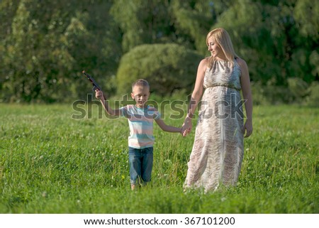 Young beautiful pregnant woman walking with her young son
