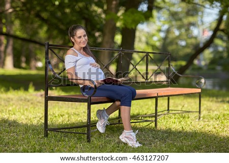 Young beautiful  pregnant  woman with book  sits on the bench in the park.