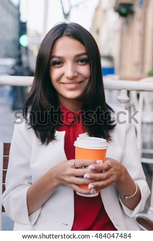 Young beautiful pretty girl outdoor with cup of coffee
