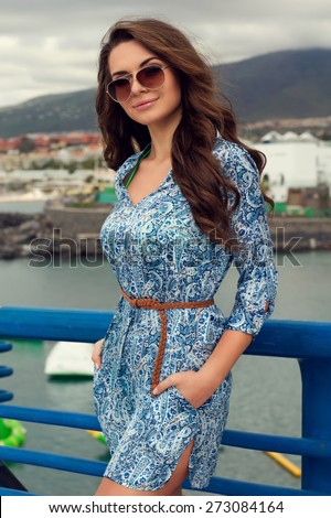 Young beautiful pretty girl posing outdoors. Summer portrait of yong stylish woman with long curly hair - stock photo