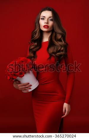 Young beautiful pretty girl standing and holding white box with red roses. Vogue fashion style studio portrait of sexy girl in red dress - stock photo