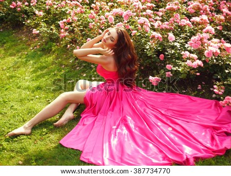 Young beautiful pretty girl with curly hair in pink silk dress sitting on grass near bushes of roses in blossom