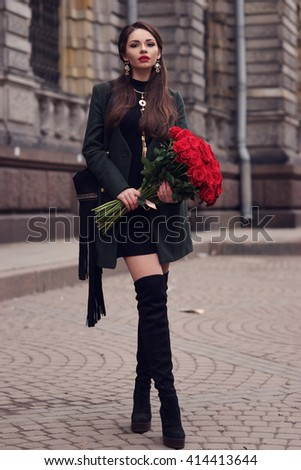 Young beautiful pretty stylish dressed girl in black dress, green jacket and high boots walking along the street in the city with big bouquet of red roses