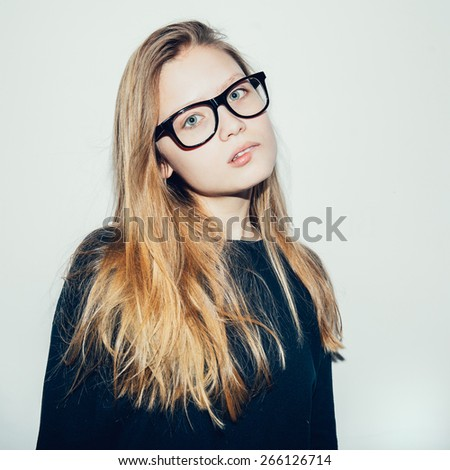 Young beautiful pretty woman looking at camera. Fashion girl hipster in glasses.Toned