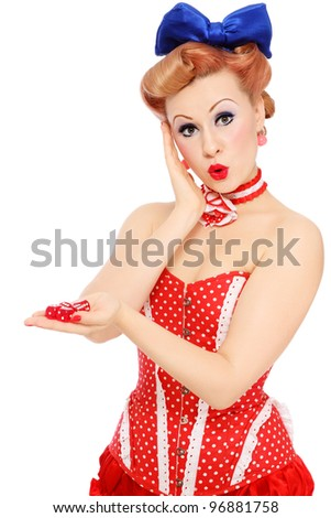Young beautiful promo pin-up girl in vintage polka dot corset with red dice in hand and surprised expression, over white background
