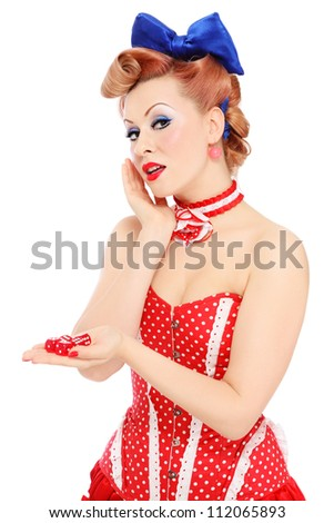 Young beautiful promo pin-up girl in vintage polka dot corset with red dice in hand over white background