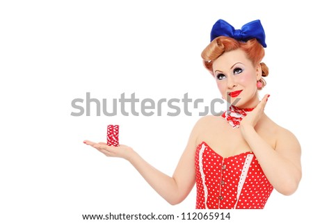 Young beautiful promo pin-up girl in vintage polka dot corset with red dice in hand over white background, copy space - stock photo
