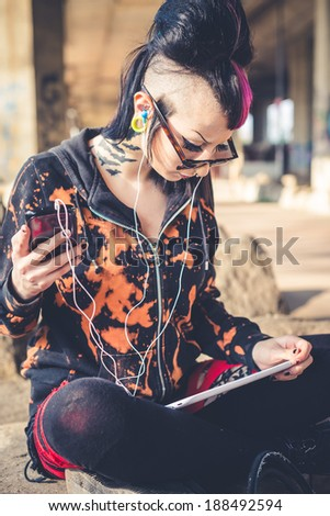 young beautiful punk dark girl using tablet in urban landscape - stock photo