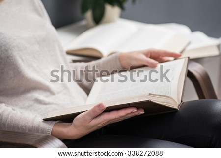 Young beautiful reading a book in a cozy chair - stock photo