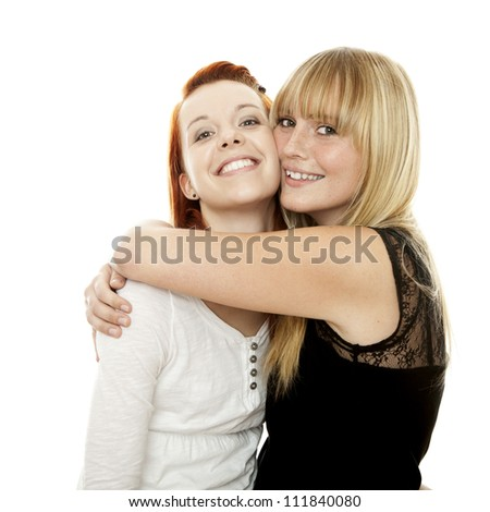 young beautiful red and blond haired girls hugs in front of white background
