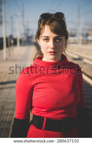 young beautiful red dressed vintage hipster woman in street town - stock photo
