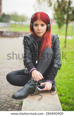 young beautiful red hair venezuelan woman lifestyle in the city of milan outdoor street listening music with headphones