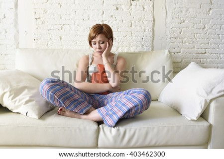 young beautiful red hair woman holding hot water bottle in a hurting tummy suffering stomach cramp and period pain sitting on home couch in painful face expression female menstruation concept - stock photo