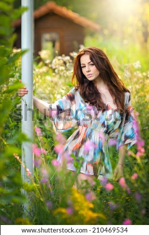 Young beautiful red hair woman in multicolored blouse in a sunny day. Portrait of attractive long hair female in the middle of wild flowers, outdoor shot. Pretty girl enjoying the nature in summer - stock photo