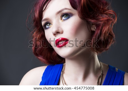 Young beautiful red-haired caucasian woman in blue dress posing in studio on gray background, professional makeup and hairstyle, expressive portrait - stock photo