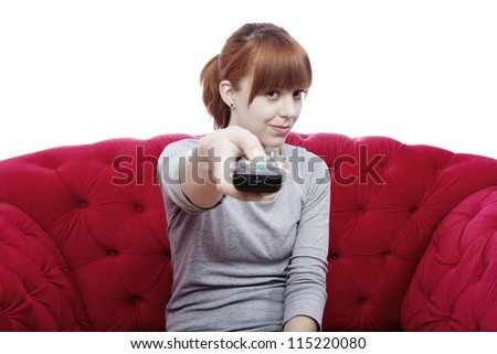 young beautiful red haired girl changing channel on red sofa in front of white background