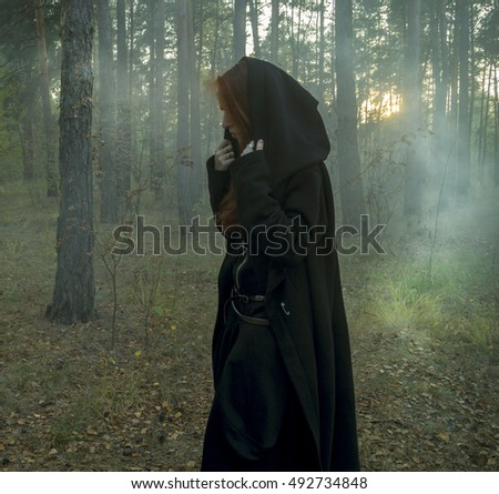 Young beautiful red-haired girl dressed like a witch in a black gown and dark clothes, with long hair, looks like a fox,  holding animal skull,  runes and tarot in the autumn forest. Divination