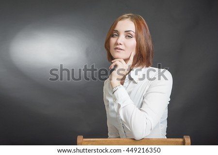 Young beautiful red-haired girl in a white blouse on a chair . Portrait on a black background