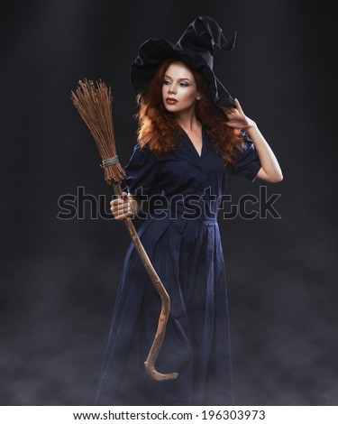 Young beautiful red-haired witch with a broom in the dark fog