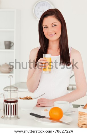 Young beautiful red-haired woman drinking a glass of orange juice in the kitchen in her apartment