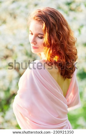 Young beautiful red-haired woman in blooming garden (selective DOF) - stock photo