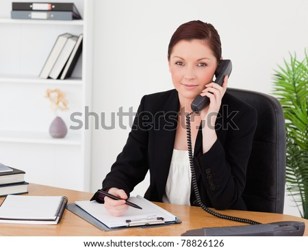 Young beautiful red-haired woman in suit writing on a notepad and phoning while sitting in an office