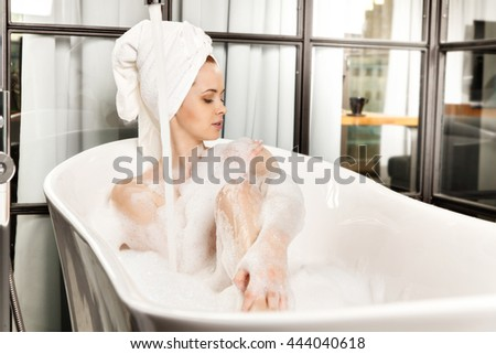 Young beautiful red-haired woman takes bubble bath. Concept of care of body. - stock photo