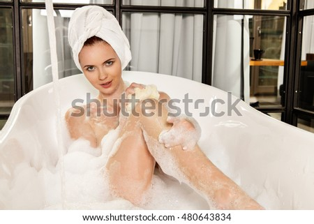 Young beautiful red-haired woman takes bubble bath. Concept of care of body.