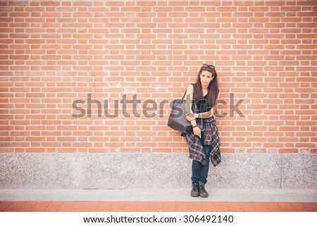 Young beautiful reddish brown hair caucasian girl posing leaning against a wall looking in camera - carefreeness, freshness, youth concept - dressed blue jeans and black shirt - stock photo