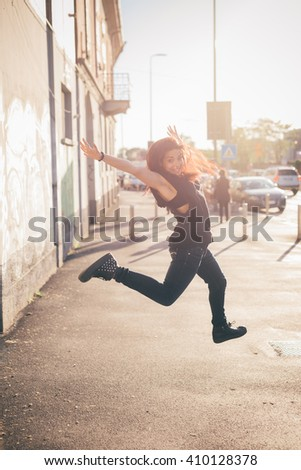 Young beautiful reddish brown hair Caucasian woman jumping, in the street looking in camera smiling - carefree, youth, freshness concept - dressed with blue jeans and black shirt. - stock photo