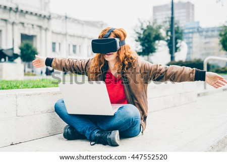 Young beautiful redhead caucasian woman sitting with laptop on his knee using 3D viewer spreading arms wide open- futuristic, multitasking, technology concept - stock photo