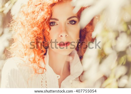 young beautiful redhead woman in white long dress posing outside in the garden in the sun, red lips, European style, Italy, France, outdoor portrait, close up, ginger, red lips stick - stock photo