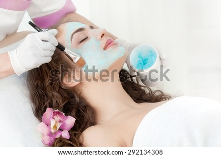 Young Beautiful Relaxing Woman Having Moistening Mask Applied - stock photo